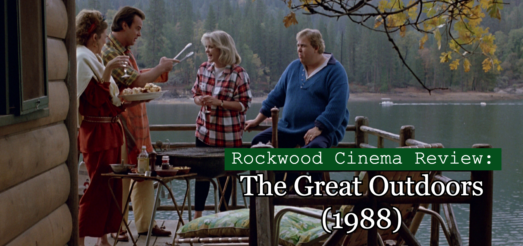 Scene from The Great Outdoors with John Candy, Stephanie Faracy, Annette Bening and Dan Aykroyd outdoors on a patio by a lake.