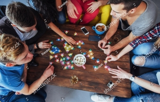stock-photo-top-view-creative-photo-of-friends-sitting-at-wooden-table-friends-having-fun-while-playing-board-574535947