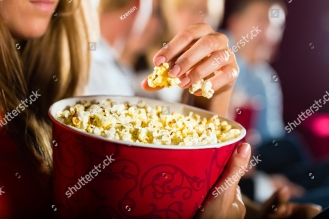 stock-photo-woman-eating-large-container-of-popcorn-in-cinema-or-movie-theater-126127955.jpg