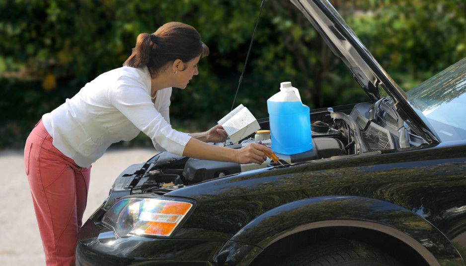 Middle age woman holding manual looking under hood of car