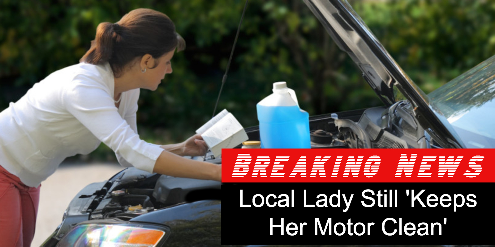 Woman doing maintenance under the hood of an SUV while holding a manual.