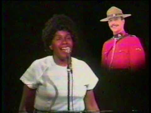BJ Snowden singing into microphone with Canadian mountie