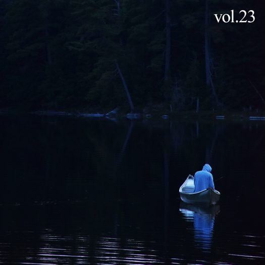 Cover of Cottage Country volume 23 with man on a dark lake in a canoe