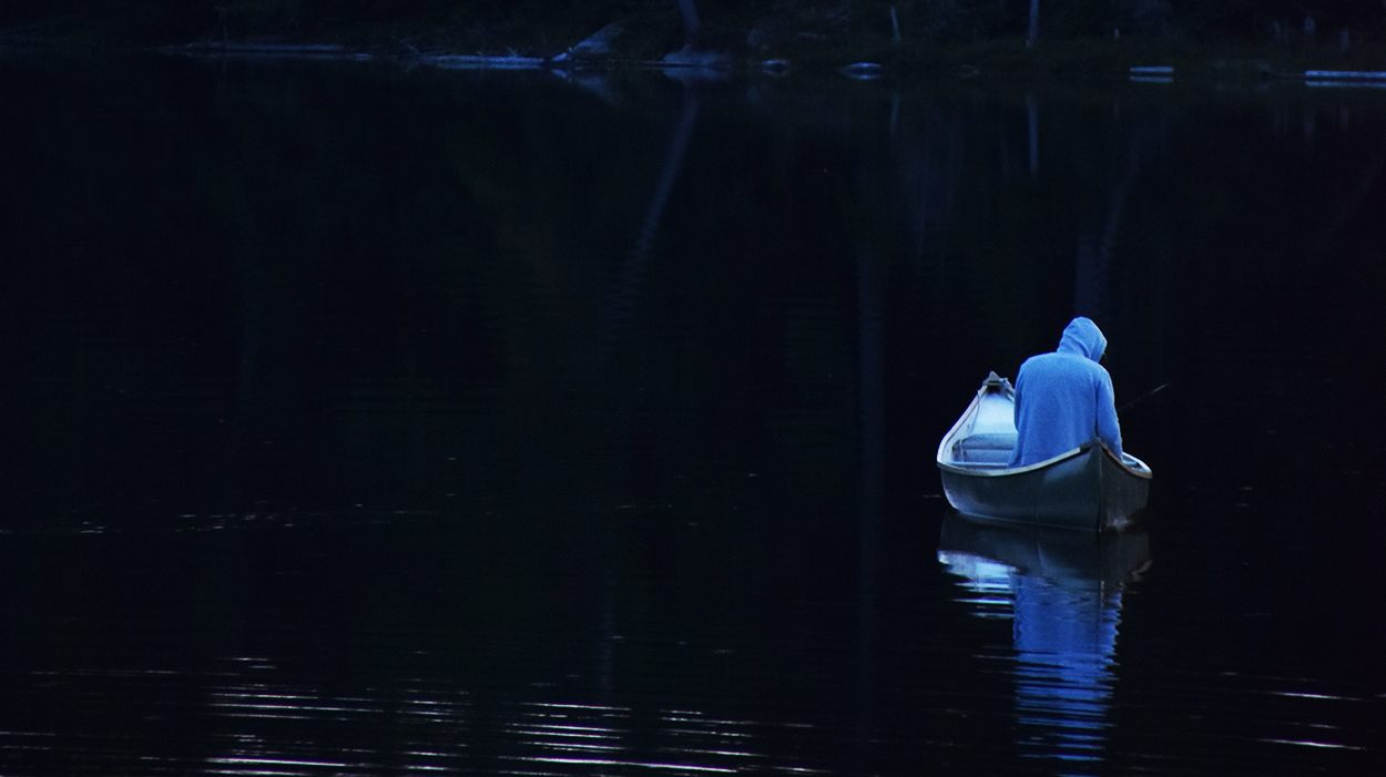 Hooded figure sitting in boat on the dark water with a reflection on a lake at dusk or dawn