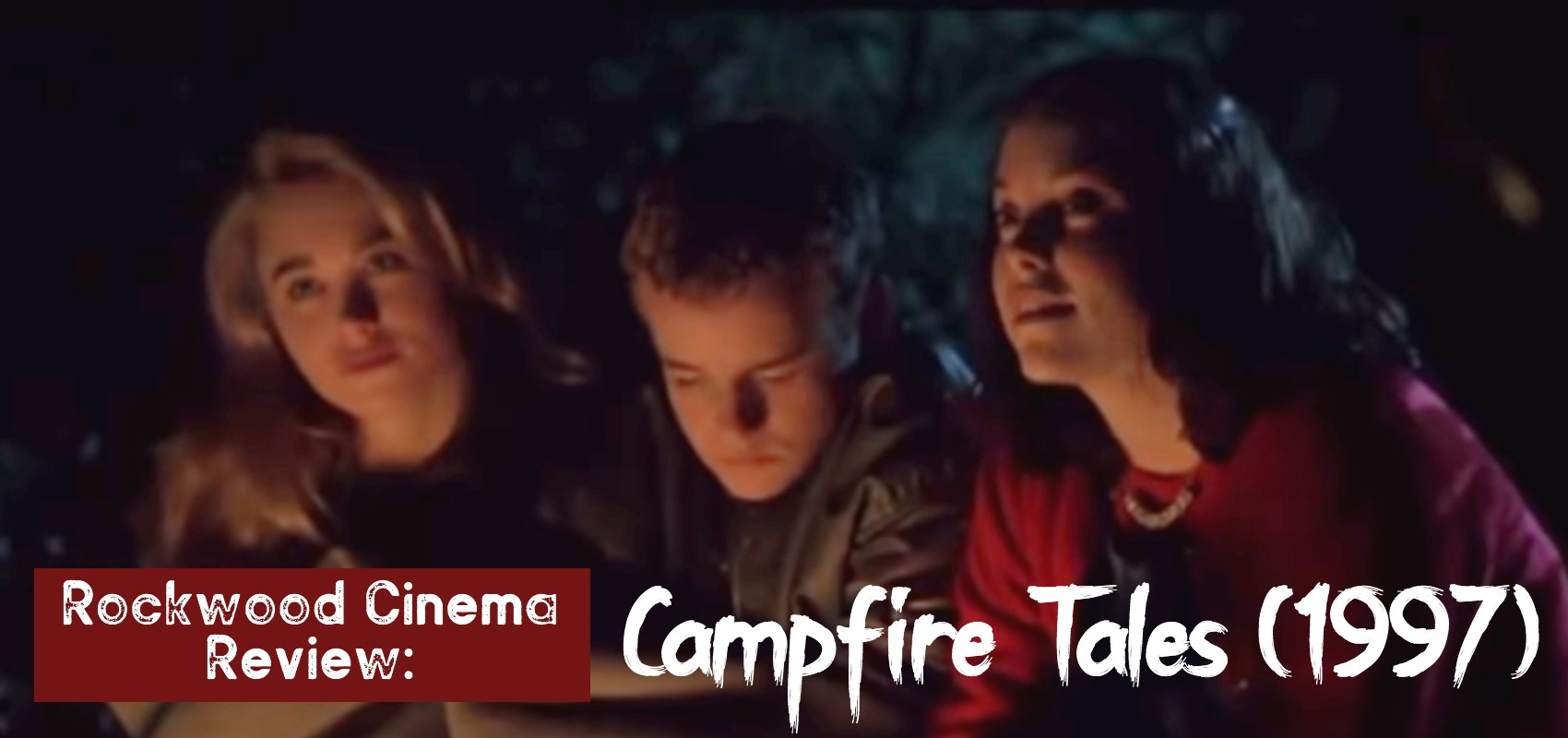 Three teens (two girls and one boy) sitting with the glow of the campfire on their face in the wooded darkness