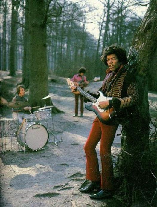 Jimi Hendrix Experience playing instruments in the woods. Jimi Hendrix is leaned against a tree wearing a military jacket