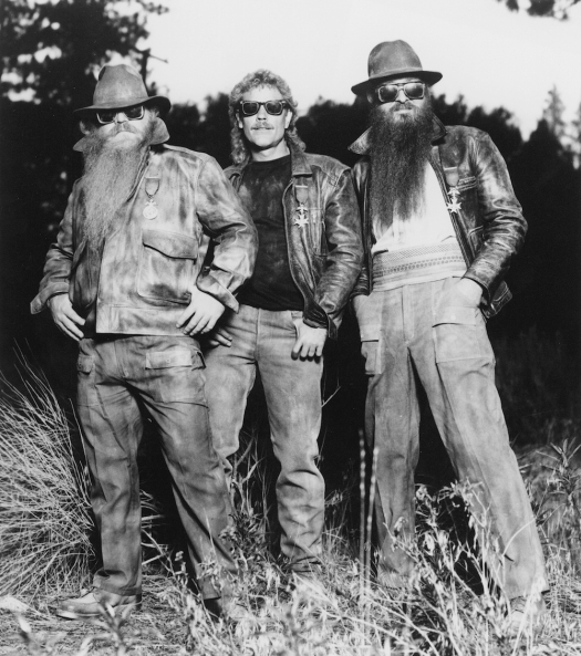 ZZ Top standing in the woods in tallish grass. They are wearing rustic clothes, vintage denim and leather jackets.