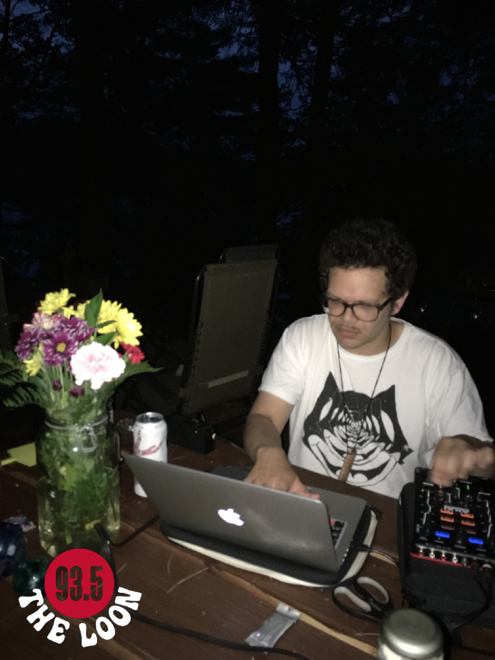 Dougie Boom DJing seated at a table in a dark forest. On the table are flowers and laptop that he is looking at.