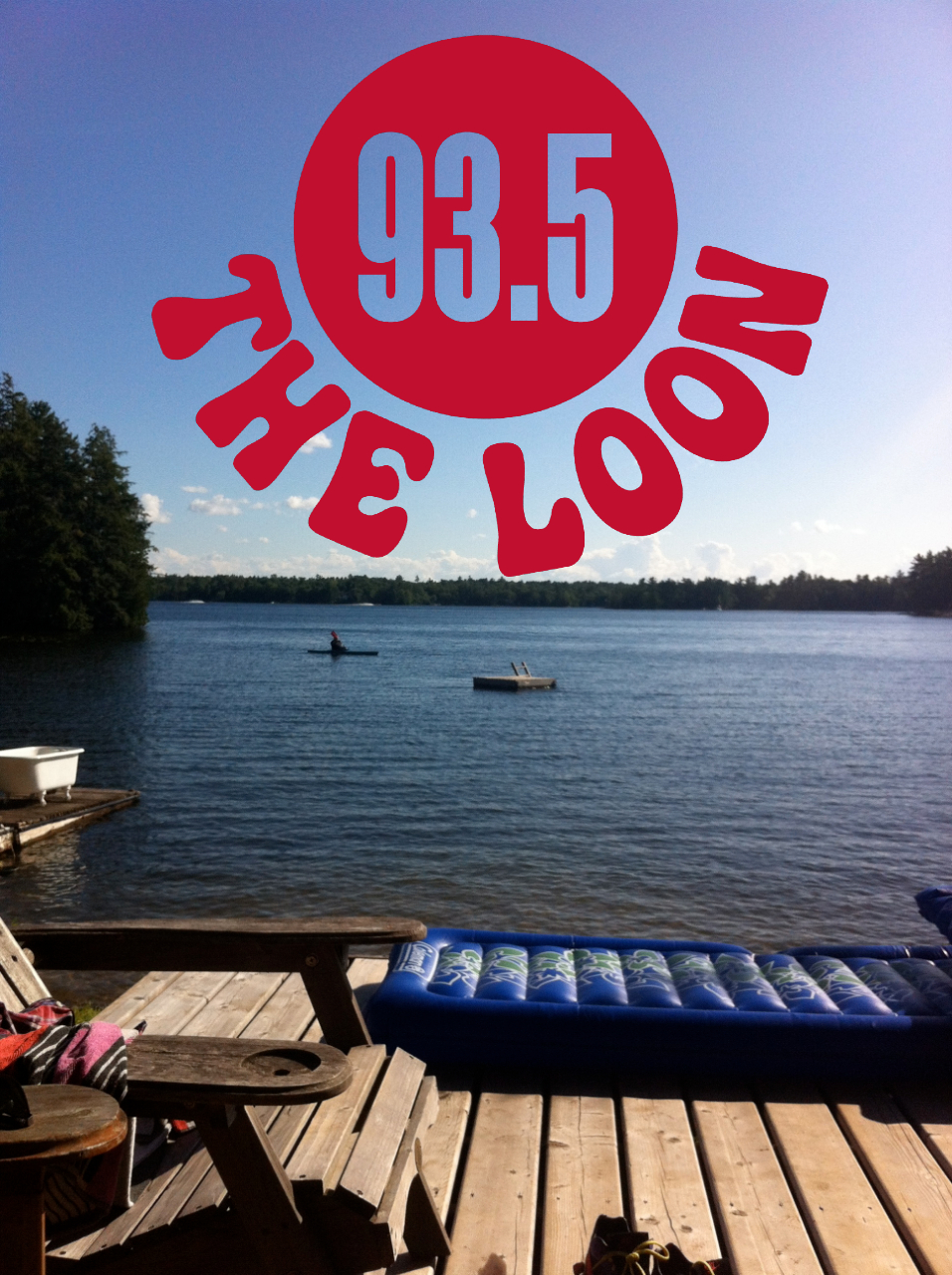 Dock near the lake with chairs and floating mattress with trees in the distance. The 93.5 Loon logo in the horizon.