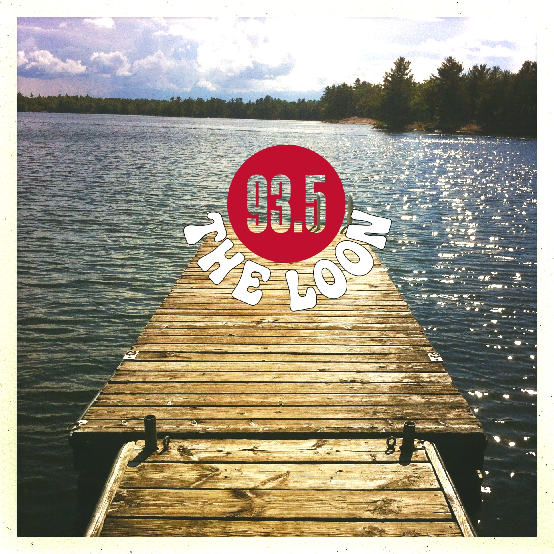 Dock stretching out into a gleaming lake with The 93.5 Loon logo in the horizon. There are trees in the distance