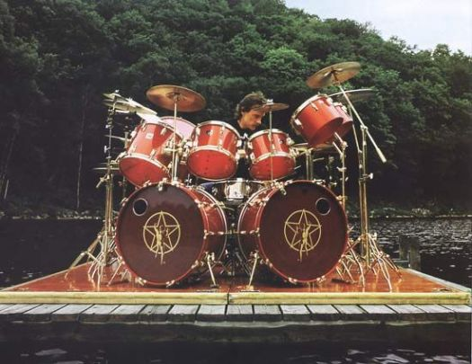 Neil Peart drumming outdoors on a dock on lake with trees in the background. The 2 kick drums have the Rush Star logo on it.