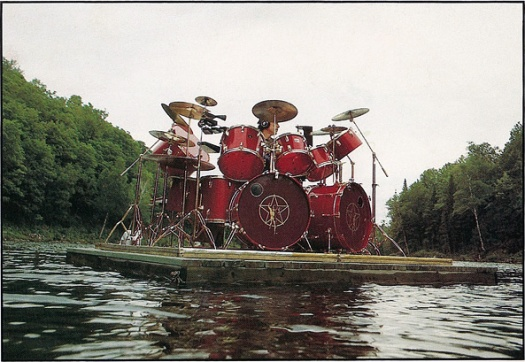 Neil Peart playing a full drum kit on a raft on a lake with surrounding trees