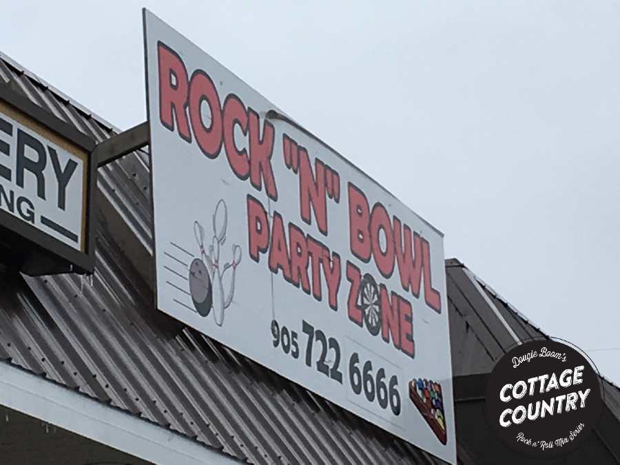 A sign that says Rock N Bowl Party Zone and has bowling ball striking down pins and triangularly racked billiard balls