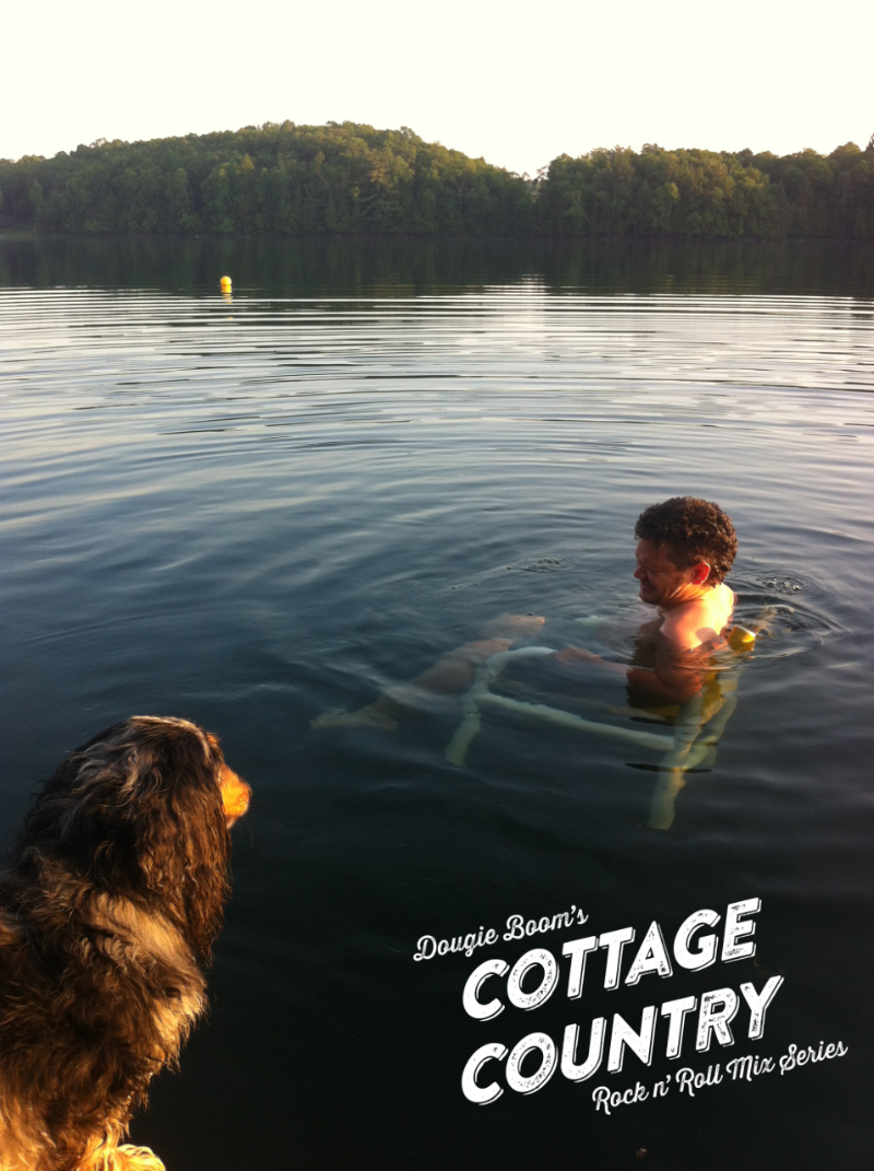 Someone sitting on a chair submerged in water on a lake with trees. A dog in the foreground stares at the man.