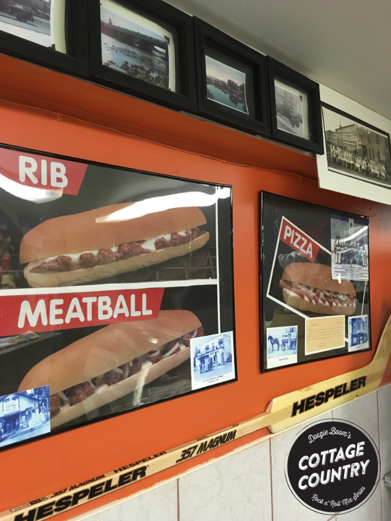 """Sub sandwiches posters (""""Rib"""" """"Meatball"""" """"Pizza"""") on restaurant wall with goalie hockey stick below."""