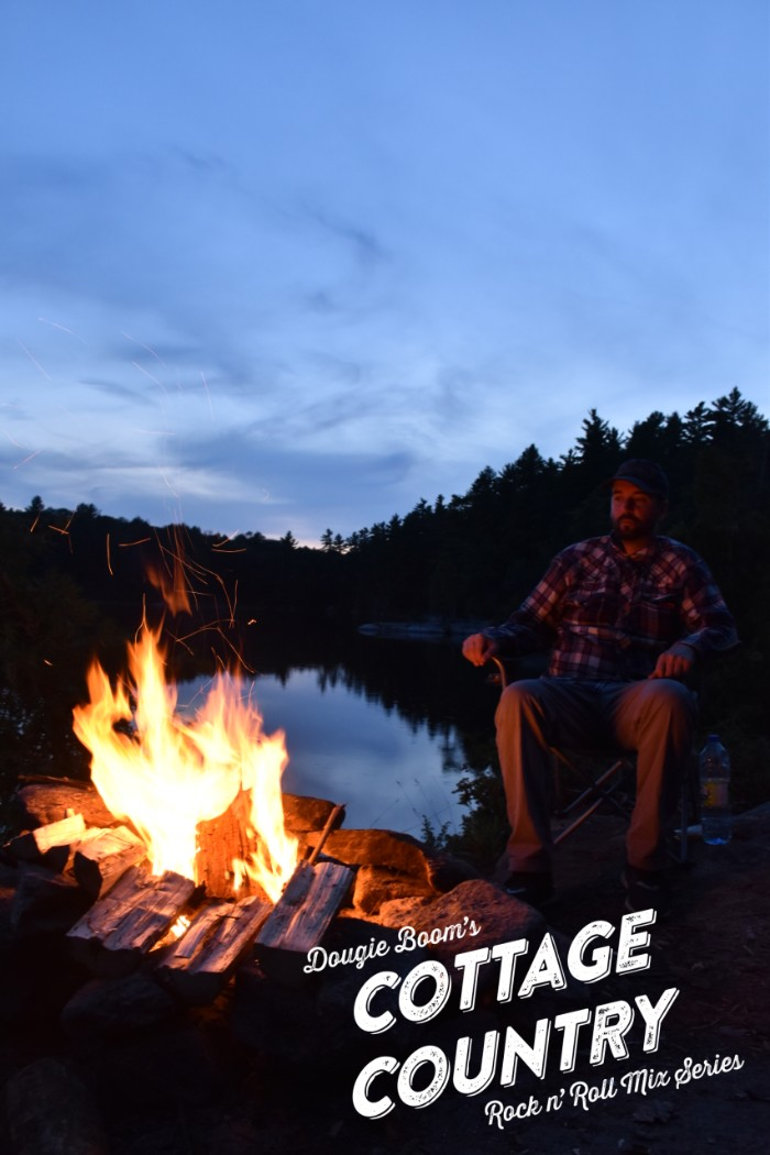 Man wearing flannel sits outdoors near a campfire. The man and forest is in the dark but the sky is a blue dusk.