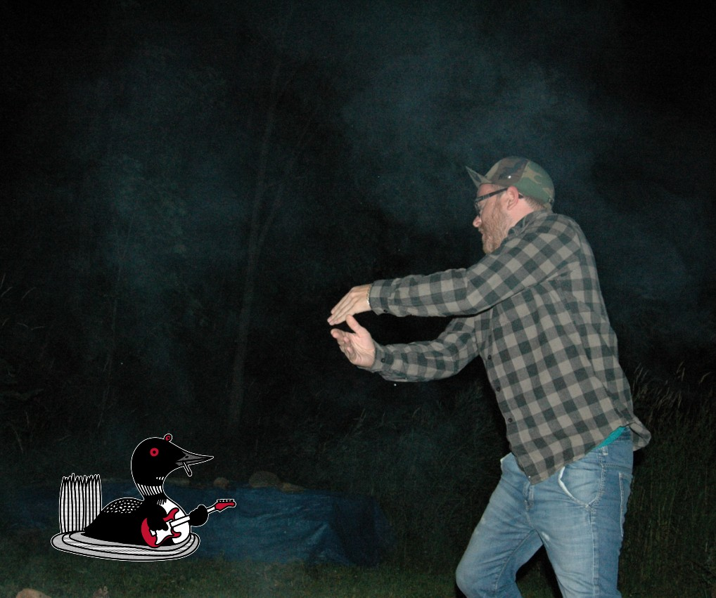 Man with flannel shirt and camo hat holds hands up to perform a charade in the dark night.