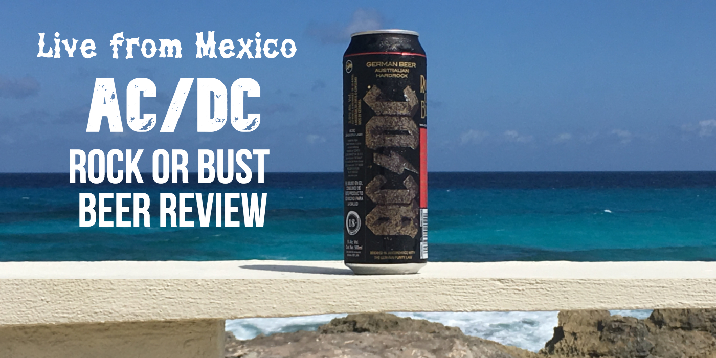 A black tall can of beer with the AC/DC logo scrolled on its side stands on a concrete ledge near the ocean