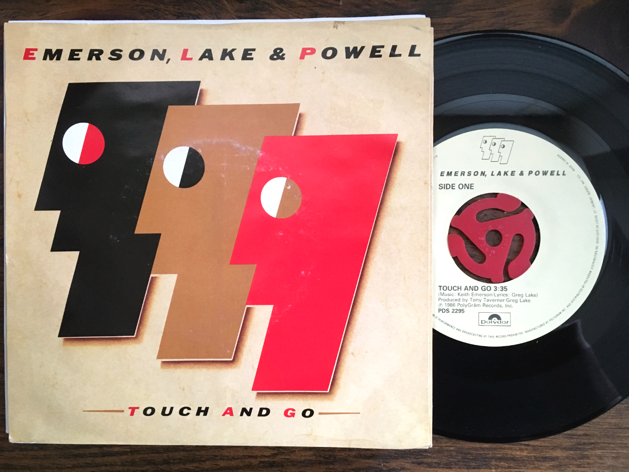 The Emerson Lake Powell Touch And Go 45 slightly out of its picture sleeve on a wooden surface.