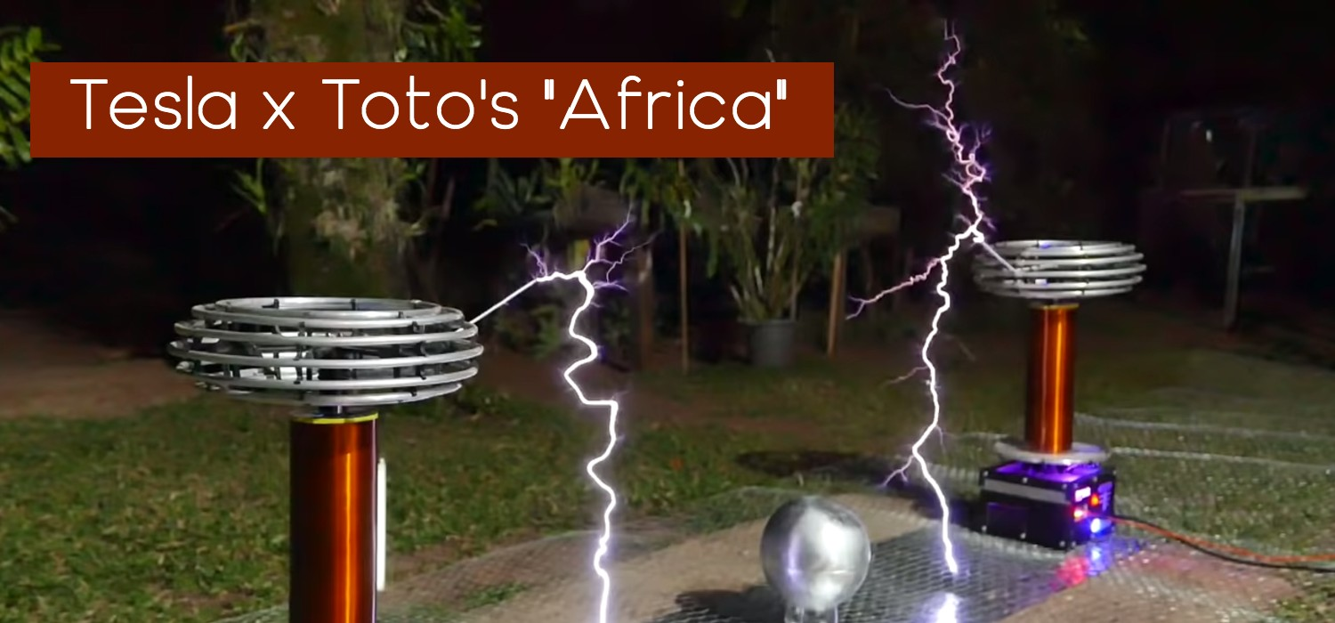 Two red Tesla coils spark with an arching current of electricity touching the metal floor between them