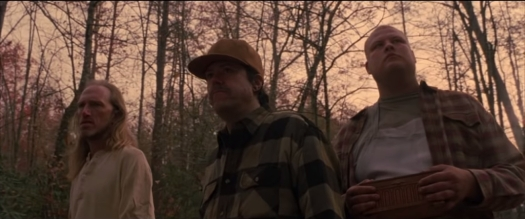 Three men (two wearing plaid and one with a trucker hat) stand menacingly in the forest