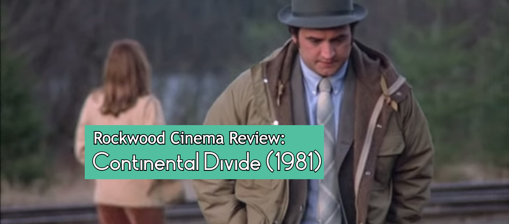 Banner for the review of Continental Divide, Jim Belushi stands near train tracks, there is a woman in background with her back turned to him.