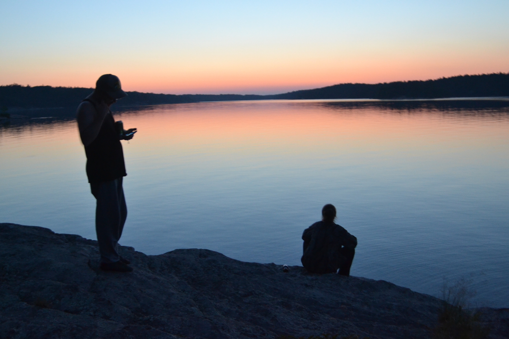 Silhouettes stand dubiously against a lake during sunset